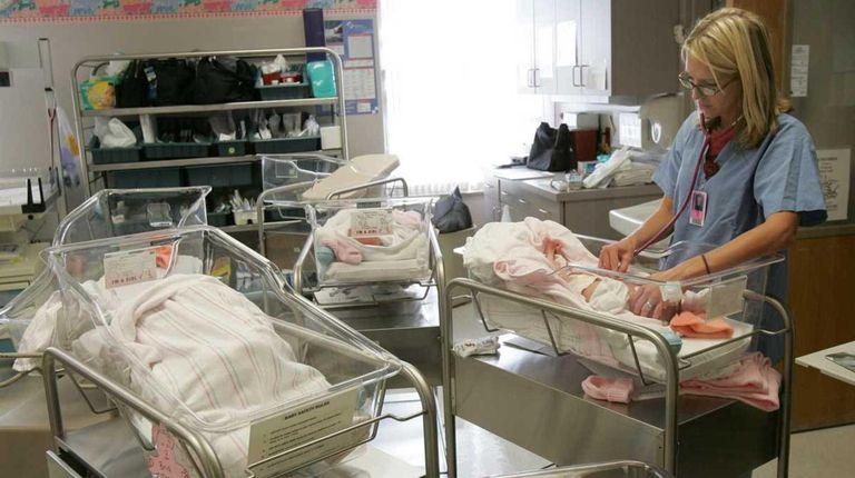 Nurse Jozie Kovar checks the heartbeat of one