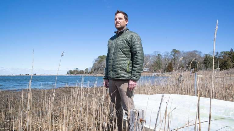 Peter Topping, the Peconic Baykeeper, stands at Red