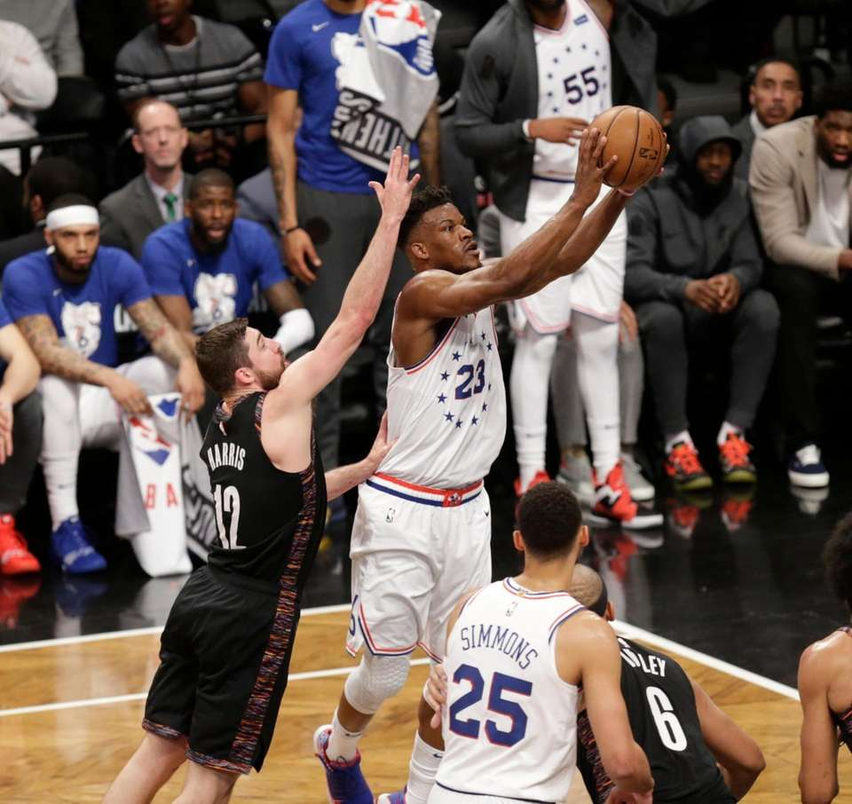 Nets forward Joe Harris (12) defends the drive