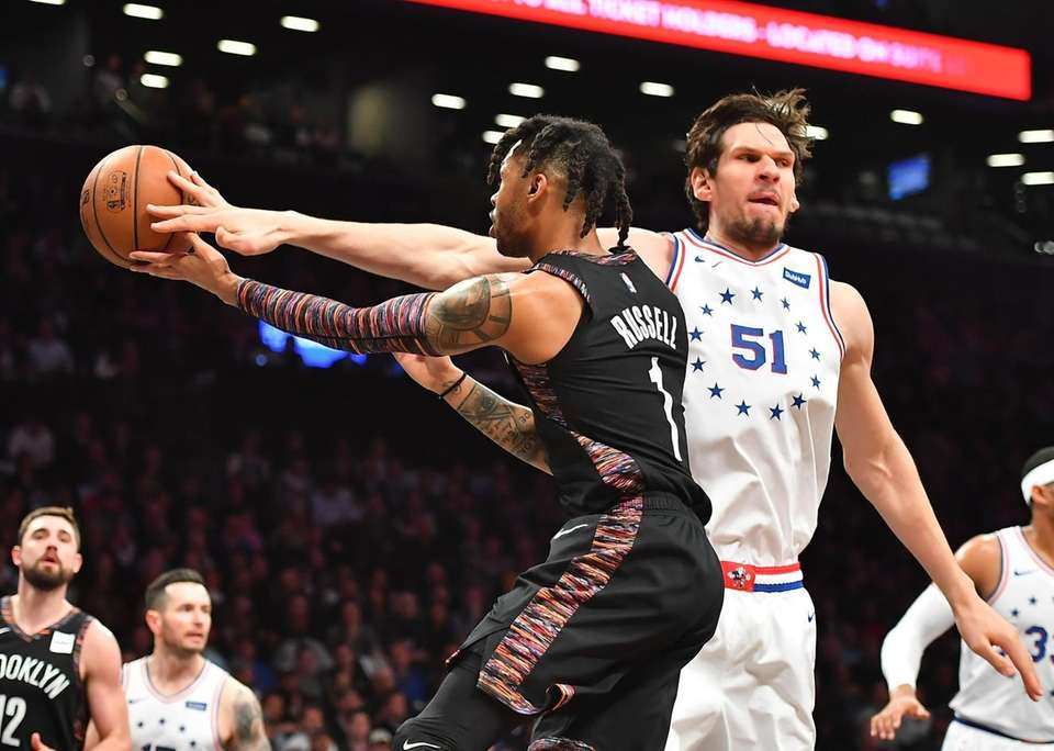 Nets guard D'Angelo Russell (1) goes around 76ers