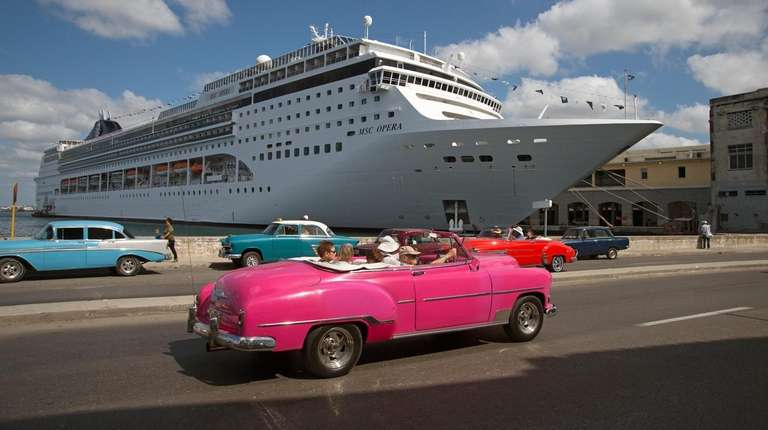A restored 1950s car drives past a docked