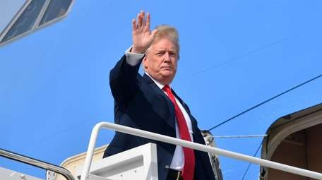 President Donald Trump waves as he boards Air