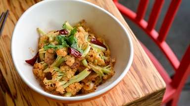 Stir-fried cauliflower topped with cilantro is served at