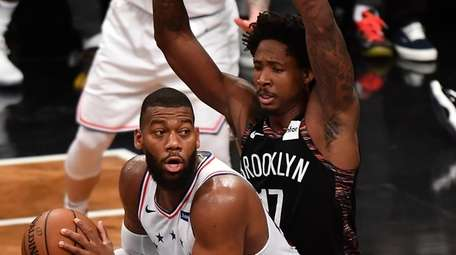 76ers center Greg Monroe is defended by Nets