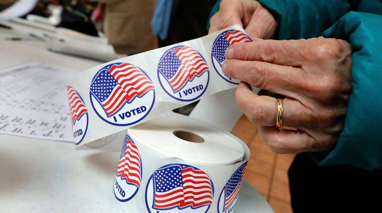 """A voter retrieves her """"I Voted"""" sticker after"""