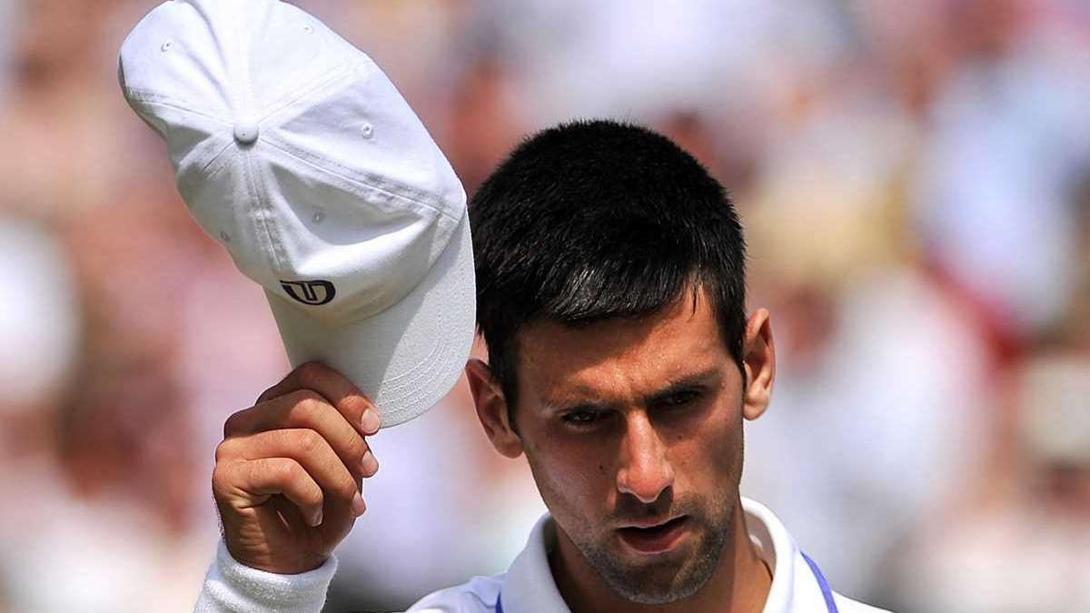 Novak Djokovic reacts as he plays with Spanish