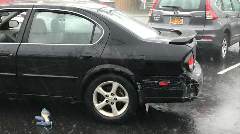 A black Nissan with damage in the parking
