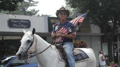 Amityville Mayor Peter Imbert rides in the village