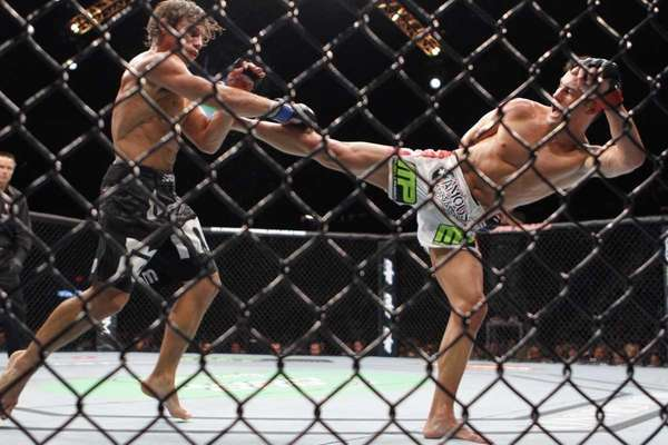 Urijah Faber, left, takes a kick from Dominick