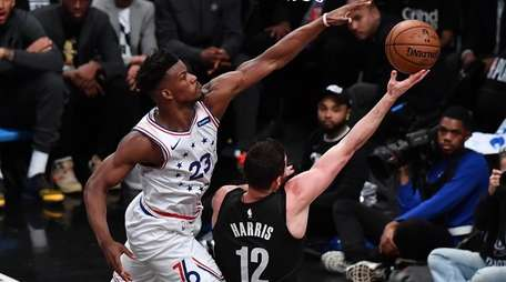 76ers guard Jimmy Butler (23) defends the drive