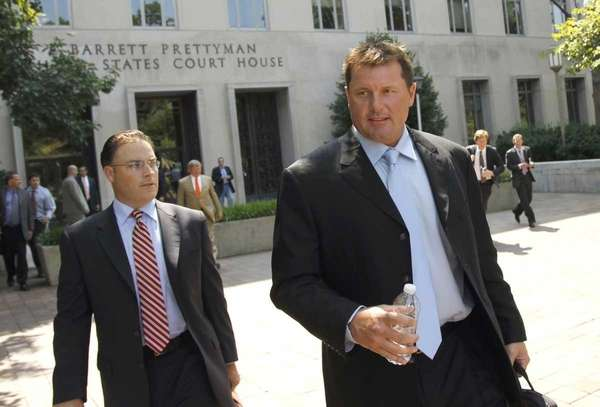 Roger Clemens, right, leaves federal court in Washington