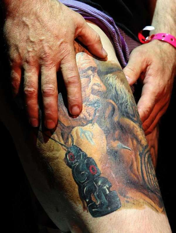 A man shows off his tattoos during the