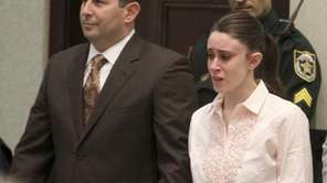 Casey Anthony holds hands with her defense attorney,