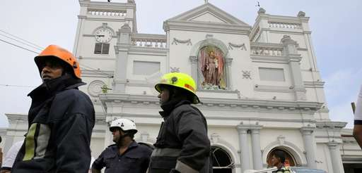 Sri Lankan firefighters stand in the area around