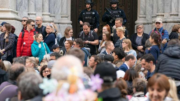 Members of the NYPD stand guard as crowds