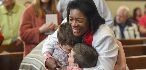 The Rev. Wendy Modeste hugs Tyler Seyda, 10,