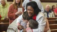 The Rev. Wendy Modeste hugs Tyler Seyda, 10,