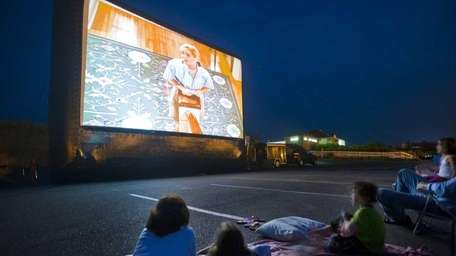 People gather for a drive-in outdoor movie at