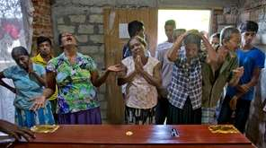 Relatives weep near the coffin with the remains