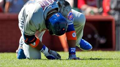 The Mets' Robinson Cano doubles over after being
