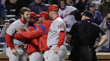 Bryce Harper, left, is restrained by coaches after