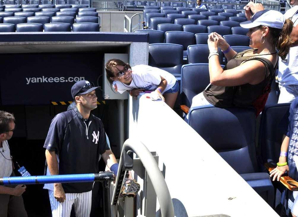 Derek Jeter poses for a photo with a
