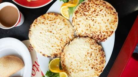 A trio of cheese covered arepas are served