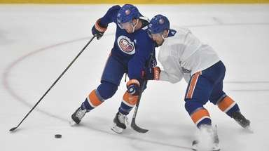 Ross Johnston of the Islanders, left, and teammate