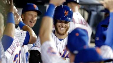 Mets starting pitcher Zack Wheeler smiles while celebrating