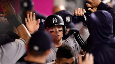 Yankees' Clint Frazier is congratulated by teammates after