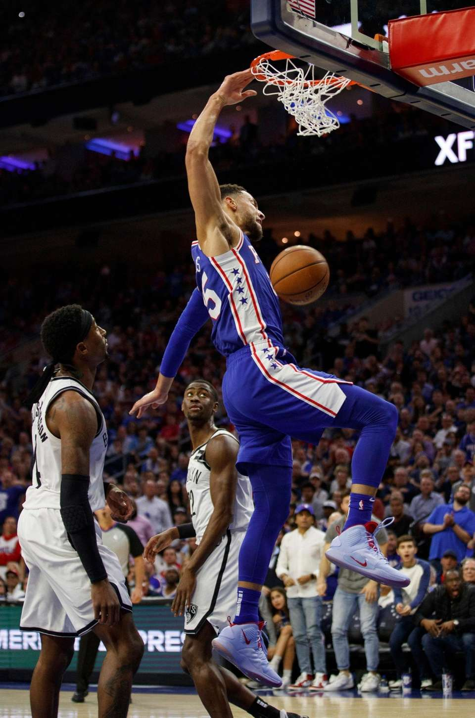 The 76ers' Ben Simmons, right, dunks the ball