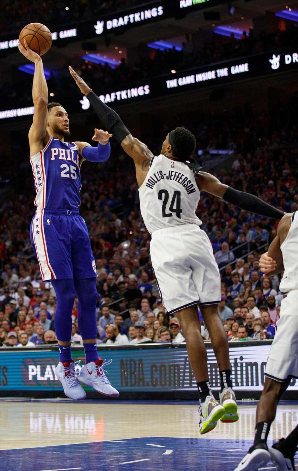 The 76ers' Ben Simmons, left, shoots the ball