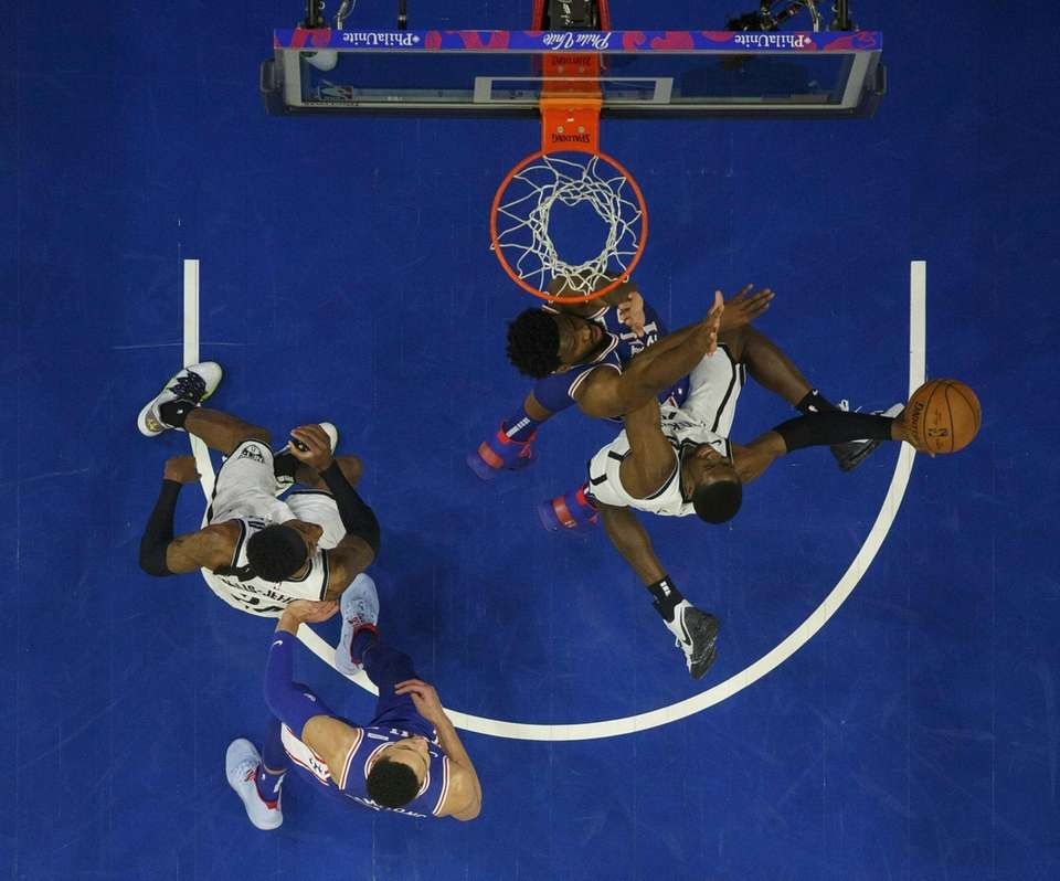 The Nets' Caris LeVert, right, goes up for
