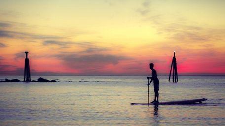 Boy paddling on the sound at dusk.
