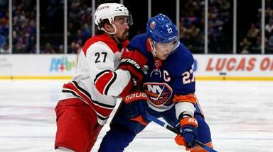 Justin Faulk of the Hurricanes checks Anders Lee