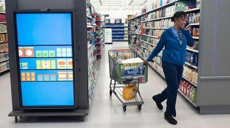 A customer pulls her shopping cart past an