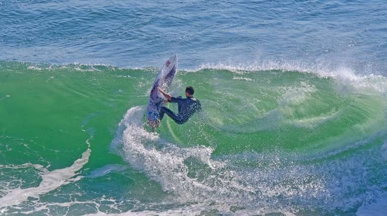 A surfer catching a wave at Turtle Cove