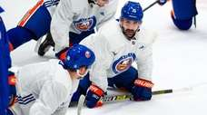 Islanders right wing Cal Clutterbuck (15) stretches with