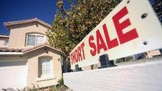 A short sale sign hangs outside a home