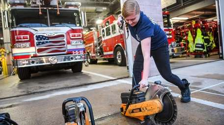 Firefighter EMT Jessica Leeb starts a saw in
