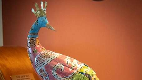 A peacock sits atop a piano in a
