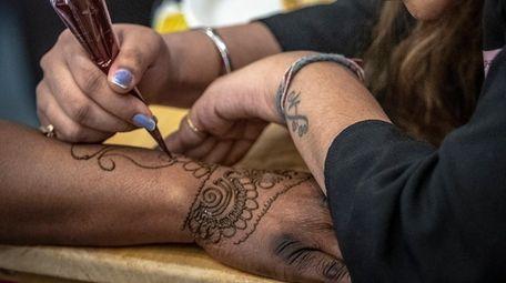 Henna artist Sonam embellishes the hand of certified