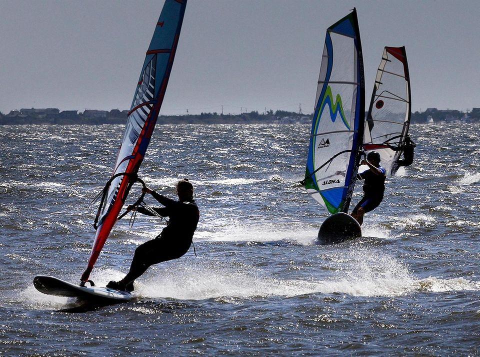 A group of windsurfers take advantage of warm