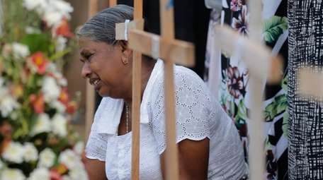 A Sri Lankan woman grieves next to the