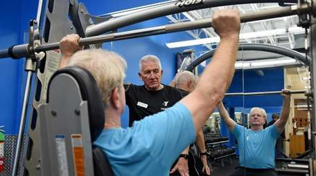 Personal trainer Wayne Ruben of Northport, center, works