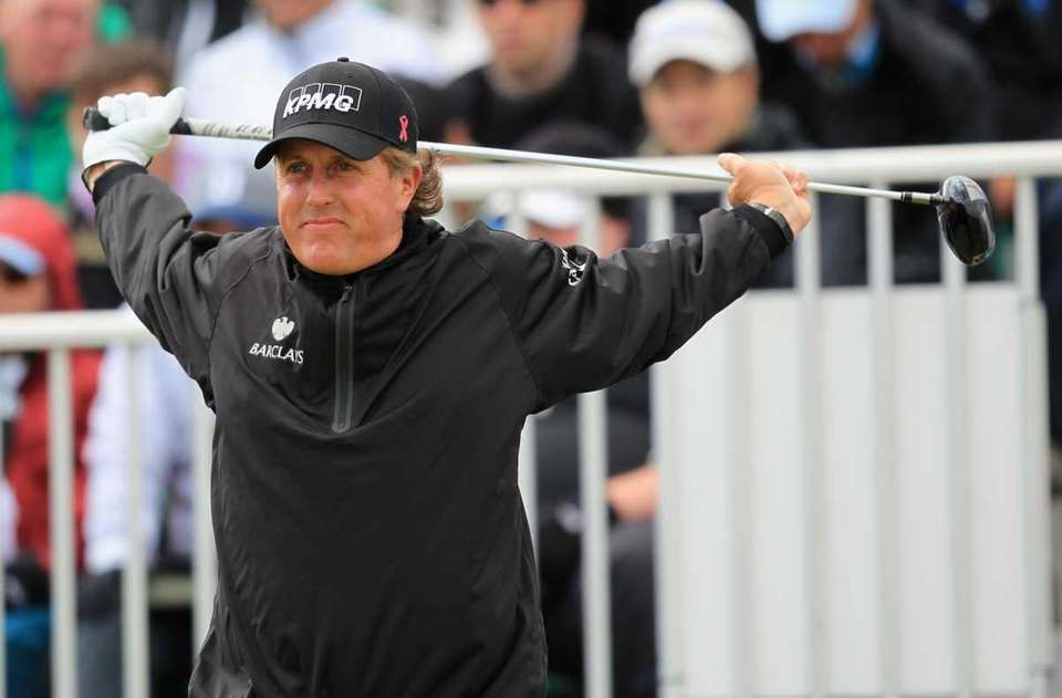 Phil Mickelson stretches on the 1st tee on