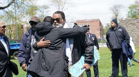 William Newallo holds his late son's skateboard at