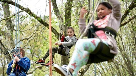 Camille Pop Smirnoff, 6, of Douglaston, center, climbs