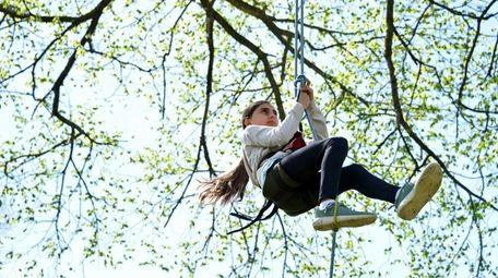 Sophia Luebker, 11, of Huntington, climbs a tree