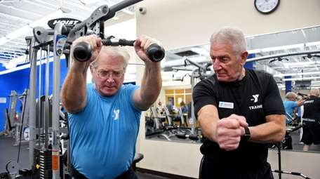 Personal trainer Wayne Ruben of Northport, right, works